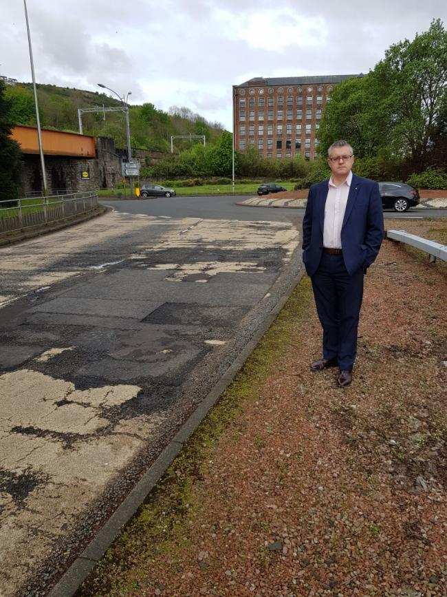 stuart mcmillan msp on the A8 at Newark roundabout which is to be resurfaced as part of a £1m project.