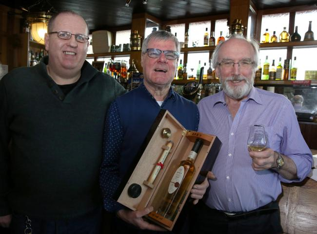 Jim Robertson of the Kempock Bar with, left, Gerry Brown and Master of Malt John Lamond, right. Jim is holding his recently acquired Spey Malt.