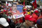 A supporter of Venezuela's President Nicolas Maduro holds up his picture during a rally in Caracas, Venezuela