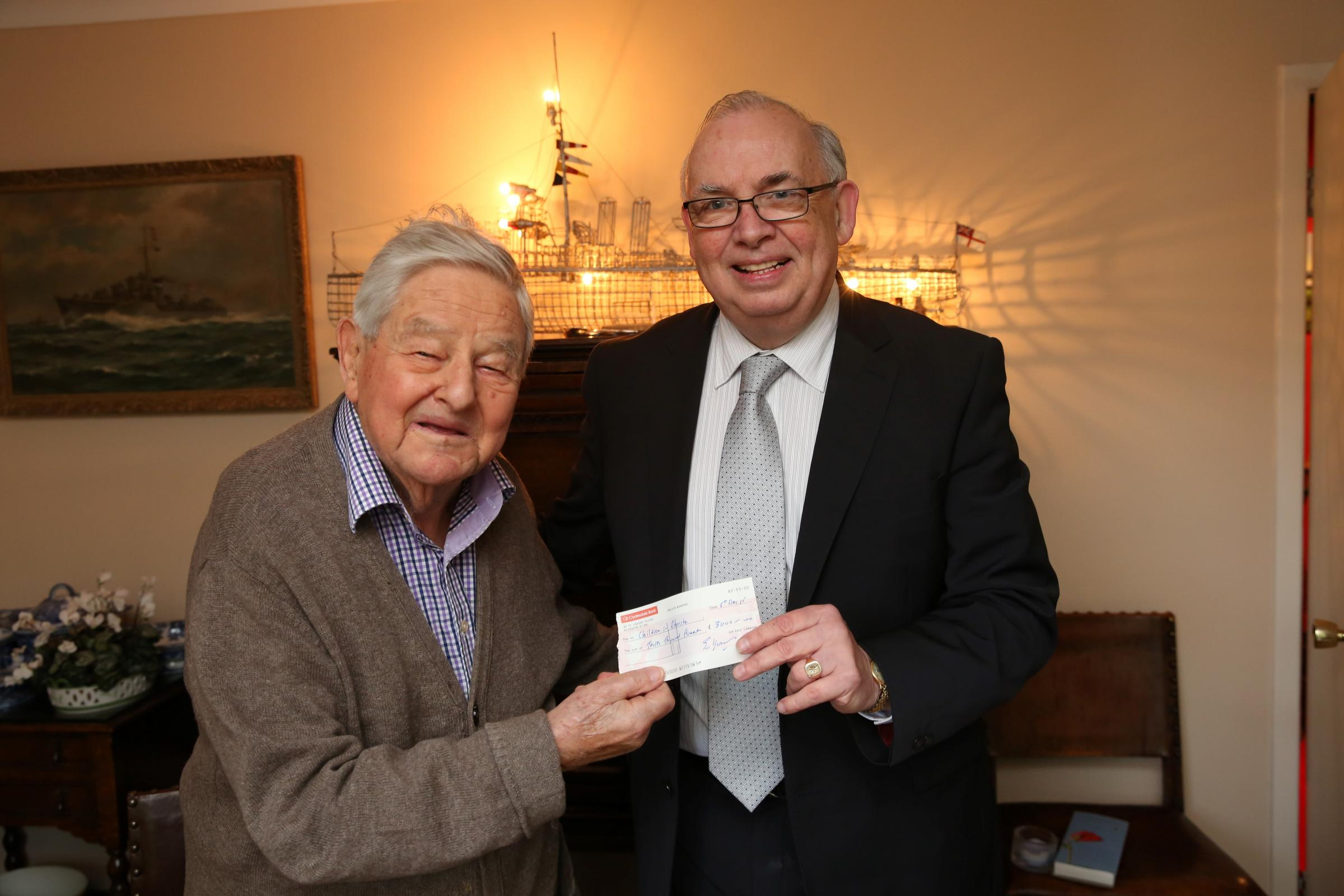 Pat Burke of Children in Poverty receives a cheque from Sir Eric Yarrow. by George Munro